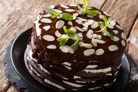 Chocolate crepes cake with whipped cream decorated with almonds and mint on a table. horizontal