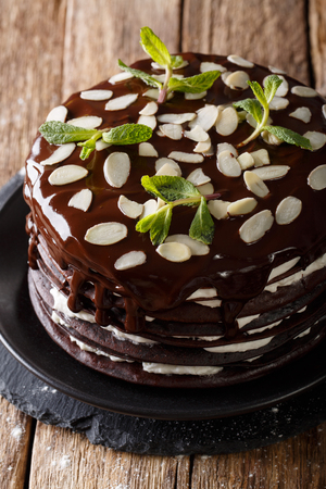 Chocolate crepes cake with whipped cream, almonds and mint on the table. vertical