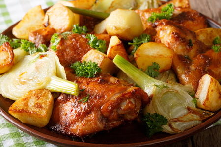 Spicy chicken baked with fennel and potatoes close-up on a plate. horizontal