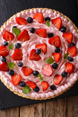 Tart with strawberries and blueberries and a pink delicate cream close-up on the table. Vertical view from above