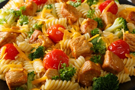Beautiful food: fusilli pasta with pork, broccoli, cheese and tomato close up. horizontal Stock Photo