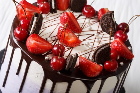 Mousse cake with fresh strawberries and cherries, decorated with biscuits and chocolate close-up. Horizontal
