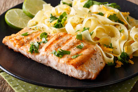 grilled salmon garnished with fettuccini pasta with cheese, herbs closeup on a plate. horizontal Stock Photo