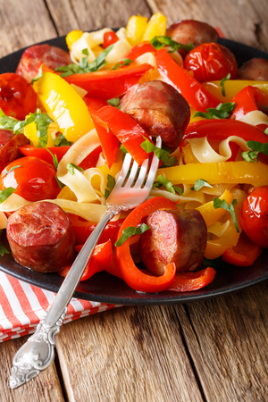 Fettuccine pasta with bell pepper, grilled sausages and tomato close-up on a plate. vertical