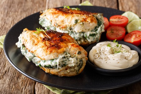 Baked Chicken fillet stuffed with cheese and spinach with sauce close-up on a plate. horizontal