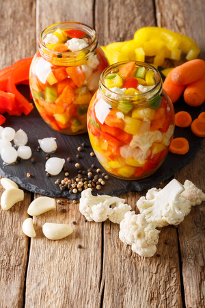 Italian Giardiniera salad of pickled cauliflower, pepper and carrots close-up in glass jars. Vertical