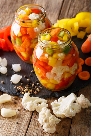 Spicy Homemade Pickled Giardiniera with Peppers, Carrots and Cauliflower close-up in glass jars. Vertical