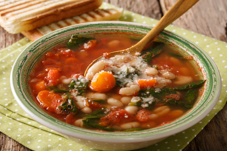 nourishing: White bean soup with tomatoes, spinach, carrots and parmesan close-up on the table. Horizontal Stock Photo