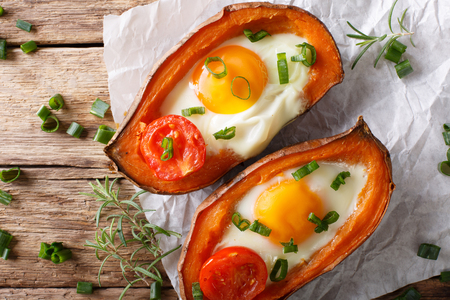 Baked yam filling with egg and tomato close-up on the table. horizontal view from above Stockfoto