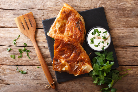 Tasty Turkish burek with spinach and cheese close-up on table. horizontal view from above
