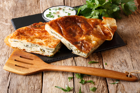 Delicious snack: Balkan burek with spinach and cheese close-up on the table. horizontal Stock Photo