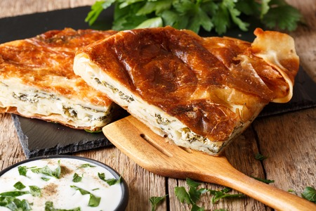 Tasty Turkish burek with spinach and cheese close-up on table. Horizontal Stock Photo