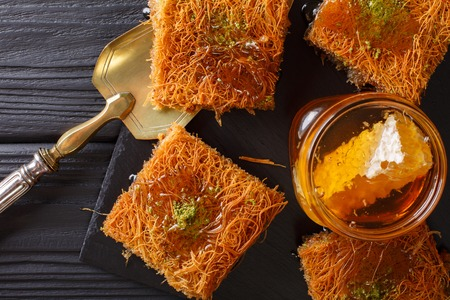 baklava: Turkish dessert kunefe with pistachio powder, Kataifi pastry close-up on a table. horizontal view from above