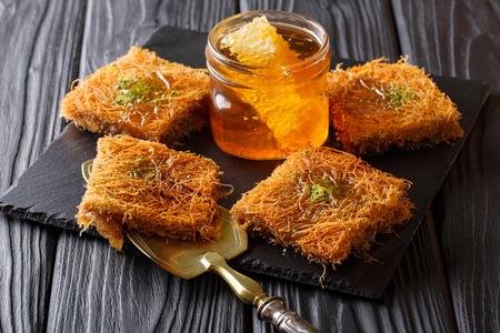 オリエンタル デザート kunafeh ピスタチオとテーブルの上の新鮮な蜂蜜のクローズ アップ。水平方向