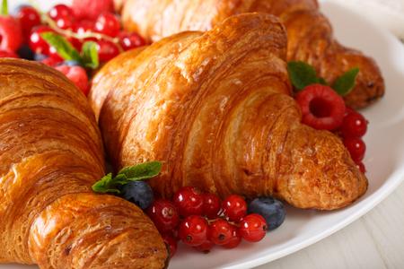 Mooie gebakjes: croissants en bessenclose-up op een plaat. horizontaal