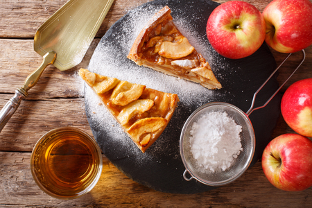 homemade piece of apple pie with powdered sugar close-up on a table. horizontal view from above