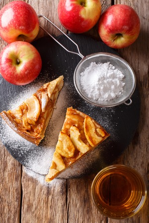 Cut freshly baked apple pie with powdered sugar close-up on the table. vertical view from above Zdjęcie Seryjne