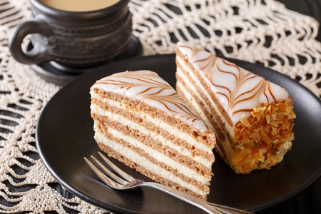 Esterhazy cake decorated with cobwebs and coffee with milk close-up on a plate. horizontal