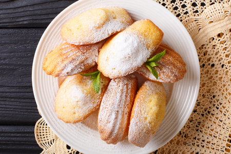 Madeleines biscuit with powdered sugar and mint closeup on a plate on the table. horizontal view from above