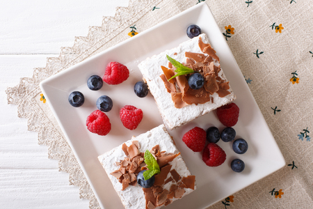 Pieces of chocolate cake with berries close-up on a plate. horizontal view from above