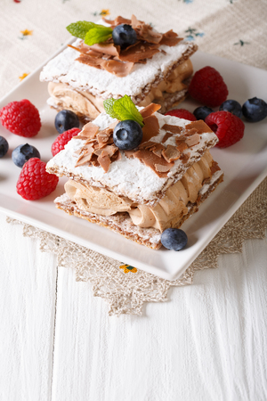 delicious chocolate millefeuille with raspberry and blueberry close-up on a plate. Vertical Stock Photo
