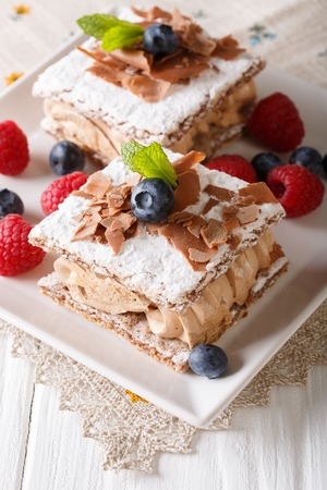Millefeuille with coffee cream, decorated with berries and mint close-up on a plate. vertical