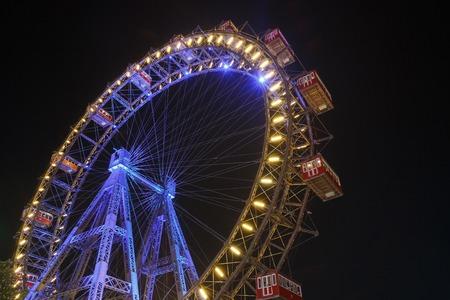 Lighting Ferris wheel at night in famous Prater theme amusement Park, Vienna. Austria
