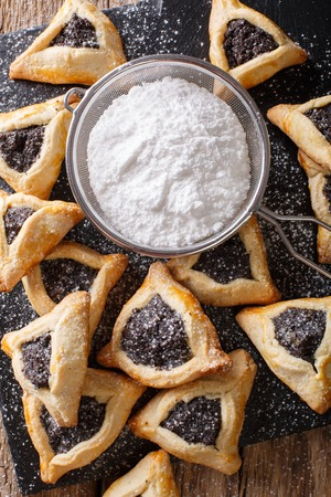 poppy seeds: Hamantaschen cookies or hamans ears Purim celebration closeup on the table. Vertical view from above Stock Photo