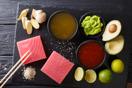 Japanese cuisine: Raw tuna steak with ingredients for cooking close-up on the table. Top view from above horizontal 스톡 콘텐츠