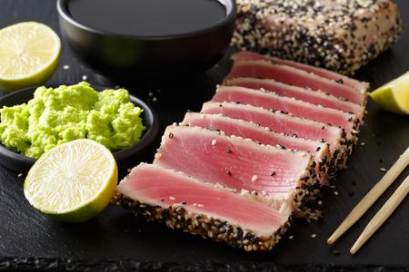 新鮮なマグロ肉のゴマと醤油、わさび、ライムがテーブルの上にクローズアップ。水平 写真素材