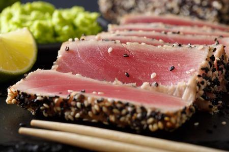 beautiful sliced tuna steak in sesame and wasabi, lime macro on the table. horizontal Stock Photo