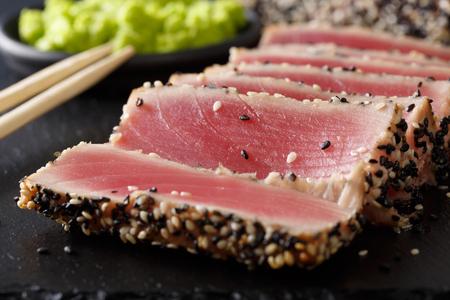 mooi eten: gesneden tonijnsteak met sesammacro op de tafel. horizontaal
