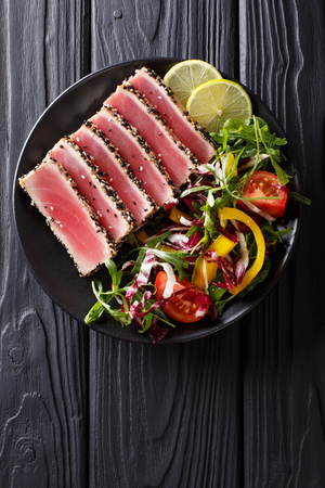 Close up of rare seared Ahi tuna slices with fresh vegetable salad on a plate. Top view from above vertical