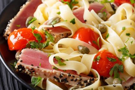 Fettuccine de las pastas con macro del filete de atún, de los tomates y de las alcaparras en una placa. horizontal