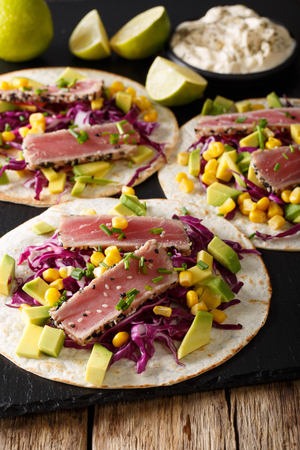 red onions: tortilla with tuna steak, sesame and fresh vegetables close-up on the table. vertical Stock Photo