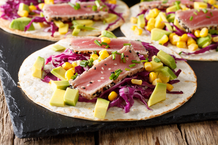 Delicious fish tortilla with tuna and fresh vegetables close-up on the table. horizontal Stock Photo