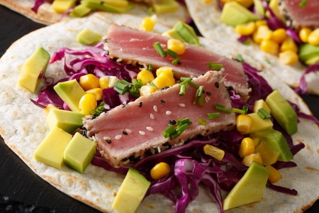 Fish tacos with tuna, red cabbage, corn, avocado and onions on the table. horizontal