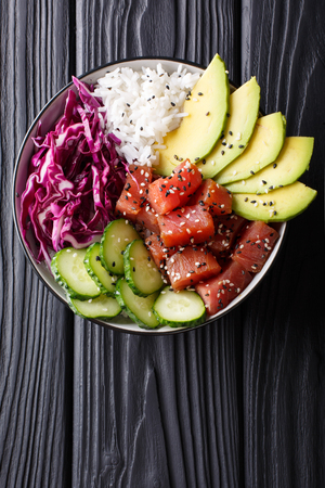 Raw Organic Ahi Tuna Poke Bowl with Rice and Veggies close-up on the table. Top view from above vertical