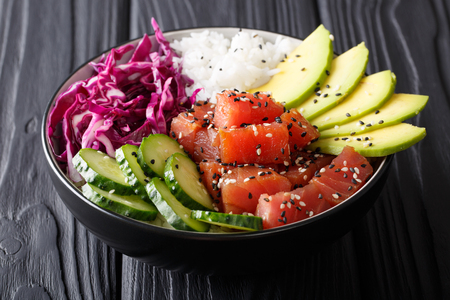 Organic food: tuna poke bowl with rice, fresh cucumbers, red cabbage and avocado close-up on the table. horizontal