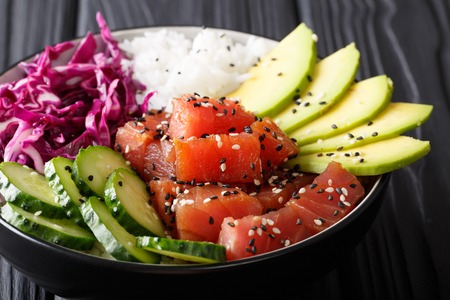 Raw Organic Ahi Tuna Poke Bowl with Rice and Veggies close-up on the table. Horizontal