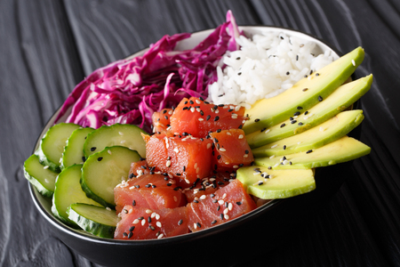 Marinated tuna poke bowl with rice, fresh cucumbers, red cabbage and avocado close-up on the table. horizontal