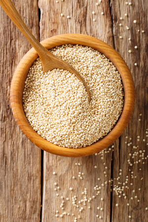 Raw quinoa close up in a wooden bowl on the table. top view from above vertical background