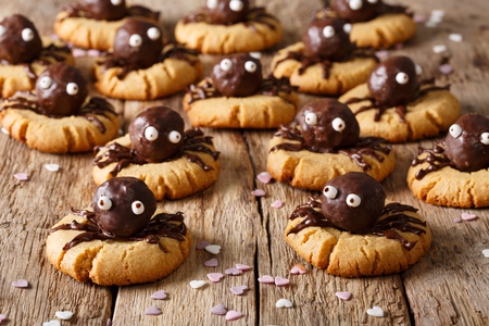 Halloween dessert: shortbread cookies with chocolate spiders close-up on a wooden table. horizontal background