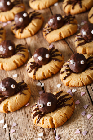 festive chocolate spider cookies for halloween on the table vertical photo