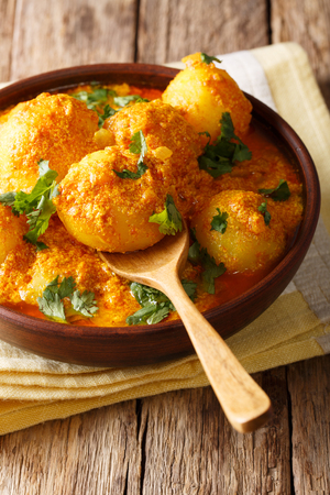 Freshly cooked Indian potatoes Dum aloo in curry sauce close-up in a bowl. verical