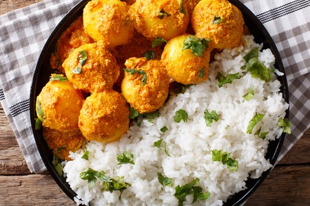freshly prepared: Freshly prepared spicy potato curry or Hot and spicy Dum aloo with rice close-up. horizontal top view from above