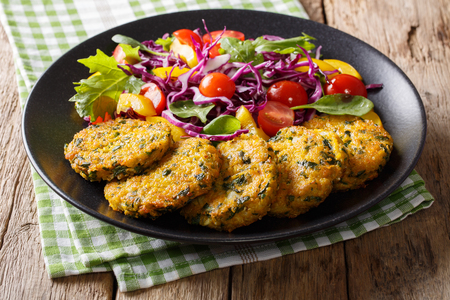 Vegetarian Food: Quinoa fritters with spinach, carrots and salad of fresh vegetables close-up on a plate. horizontal