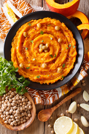Delicious pumpkin hummus with ingredients on the table close up. Vertical top view from above