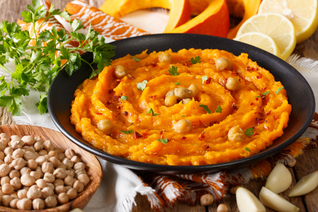 Delicious pumpkin hummus with ingredients on the table close up. horizontal