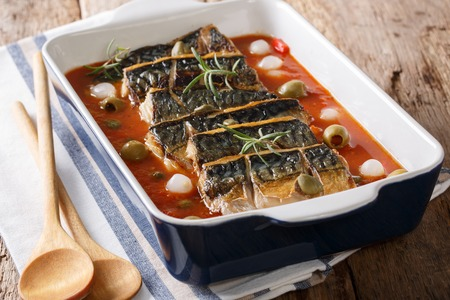 Freshly cooked mackerel fillet with vegetables in tomato sauce close-up in a baking dish on a table. horizontal Imagens